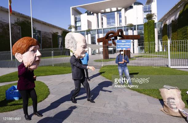 Demonstrators with German Chancellor Angela Merkel and German Federal Minister of Finance Olaf Scholz masks stage a protest German government's...