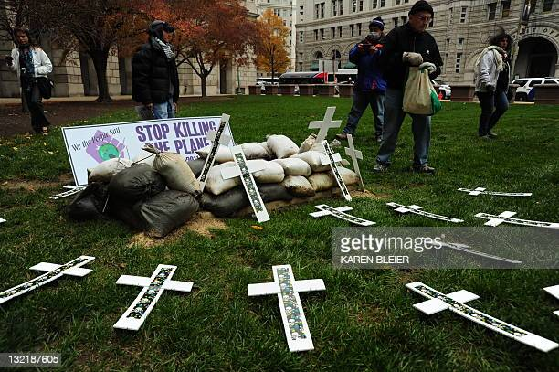 Demonstrators with Occupy Washington DCorg the No FEAR Coalition the National Whistleblower Center and the Federal Alliance place crosses on the...