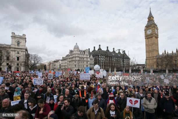 Demonstrators with placards gather in Parliament Square with the Houses of Parliament and Elizabeth Tower in the background during a rally against...