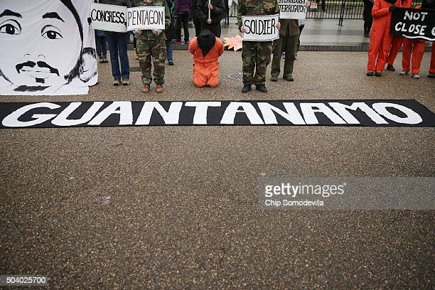 Demonstrators with the group Witness Against Torture dress in orange jumpsuits wear black hoods and hold a banner with the image of Mohammed al...