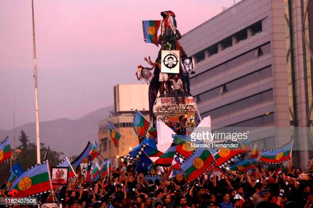 Demonstrators with the picture of Camilo Catrillanca and waving Wenufoye flags climb the monument at Plaza Italia during a protest against president...