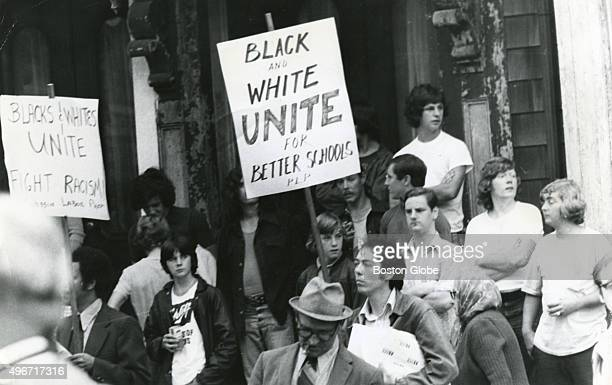 Demonstrators with the Progressive Labor Party protesting the antibusing movement hold up signs that read Black and white UNITE for better schools...