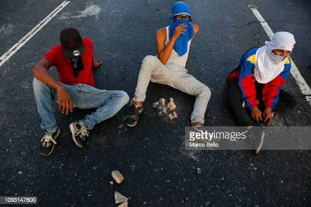 Demonstrators with their faces covered sit in the street as they protest against the government of Nicolás Maduro on February 2 2019 in Caracas...