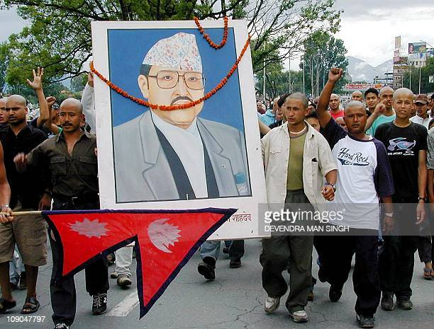 Demonstrators with their heads shaved in mourning hold a portrait of the late King Birendra after the new King Gyanendra was crowned in Kathmandu 04...
