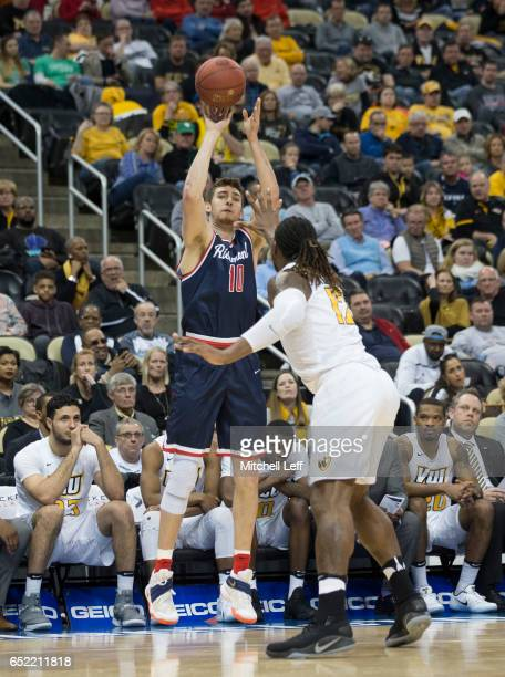 De'Monte Buckingham of the Richmond Spiders shoots the ball against Mo AlieCox of the Virginia Commonwealth Rams in the Semifinals of the men's...