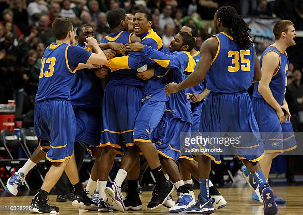 Demonte Harper of the Morehead State Eagles is mobbed by his teammates after hitting a game winning three point shot with 5.5 seconds left on the...