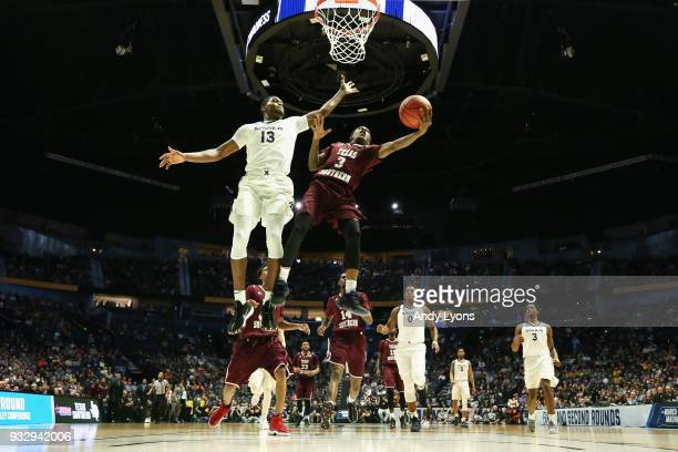 Demontrae Jefferson of the Texas Southern Tigers lays the ball up over Naji Marshall of the Xavier Musketeers during the game in the first round of...