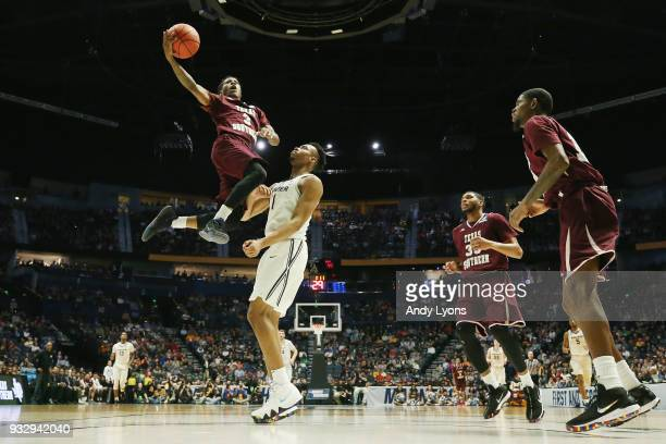 Demontrae Jefferson of the Texas Southern Tigers puts up a layup over Paul Scruggs of the Xavier Musketeers during the game in the first round of the...
