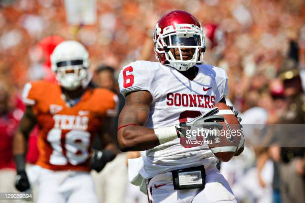 Demontre Hurst of the Oklahoma Sooners returns a interception for a touchdown against the Texas Longhorns at the Cotton Bowl on October 8, 2011 in...