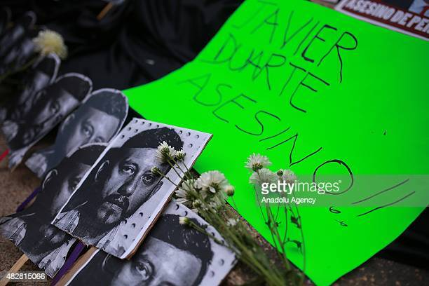 Demostrators hold banners and a portrait of Ruben Espinosa, during a protest to demand the clarification of the murder of photojournalist Ruben...