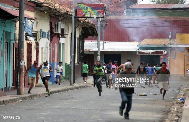 Demostrators run during nationwide protests demanding justice democracy and the departure of President Daniel Ortega in Masaya Nicaragua on May 12...