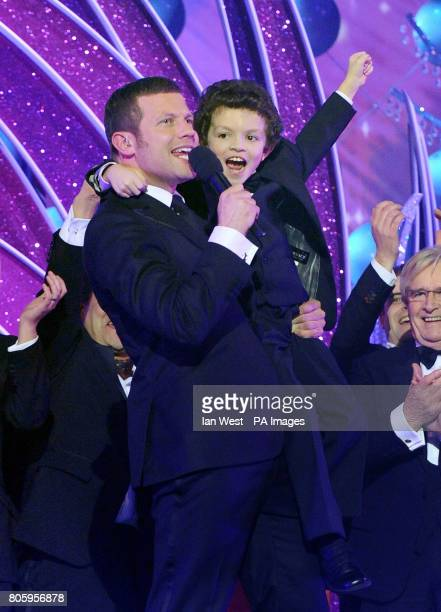 Demot O'Leary hold up young actor Alex Bain as members of the Coronation Street cast collect the best Serial Drama award during the National...