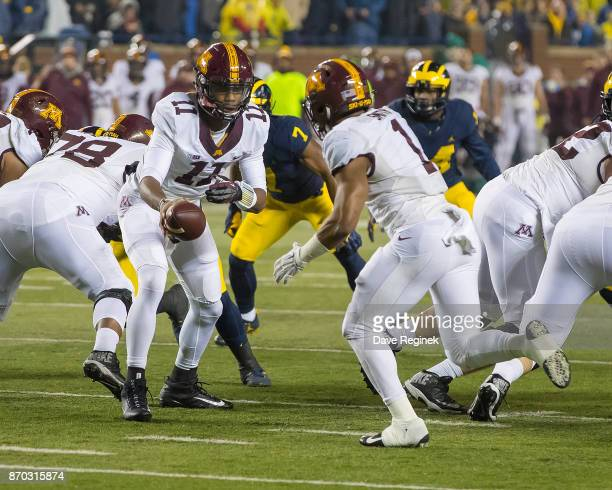 Demry Croft of the Minnesota Golden Gophers hands the football off to Rodney Smith during a college football game against the Michigan Wolverines at...