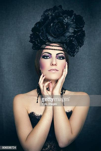 Demure gothic woman with black flower hairdo
