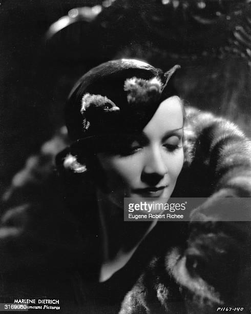 Demure Marlene Dietrich dressed in hat and fur.