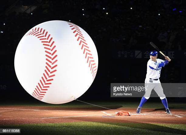 DeNA BayStars slugger Yoshitomo Tsutsugo hits a giant ballshaped balloon in a ceremony at Yokohama Stadium on April 4 ahead of a Central League game...