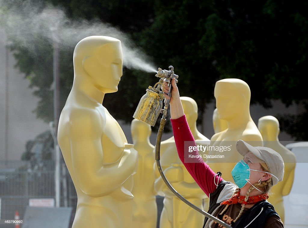 Dena D'Angelo spray paints an Oscar statue with gold color during preparation of 87th Annual Academy Awards at Dolby Theater February 18, 2015 in Hollywood, California.