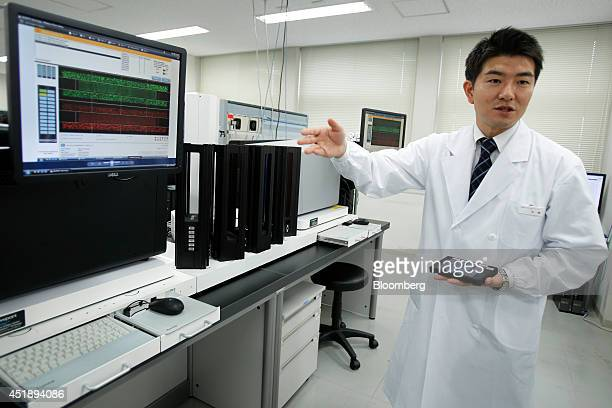DeNA Life Science Inc. Employee Hiroki Furuhashi talks to members of the media as he stands in front of a scanning device used in the preparation of...