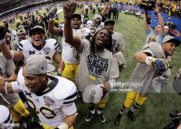 Denard Robinson of the Michigan Wolverines celebrates with teammates after Michigan won 2320 in overtime against Virginia Tech Hokies during the...