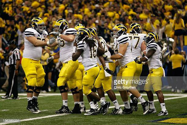 Denard Robinson of the Michigan Wolverines celebrates with his teammates after he threw a 45yard touchdown pass in the second quarter to Junior...