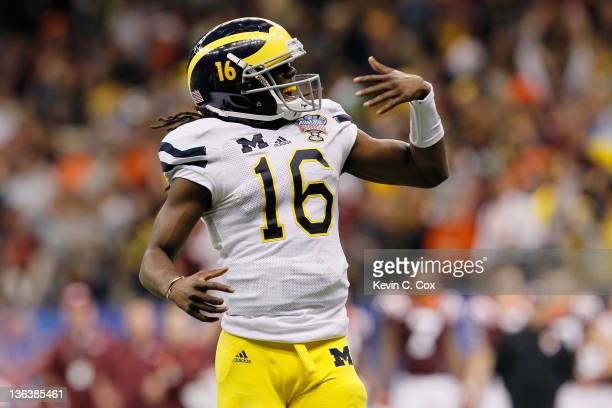 Denard Robinson of the Michigan Wolverines celebrates after he threw an 18yard touchdown pass to Junior Hemingway in the third quarter against the...