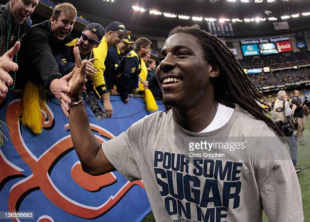 Denard Robinson of the Michigan Wolverines celebrates as he runs off of the field after Michigan won 2320 in overtime against Virginia Tech Hokies...