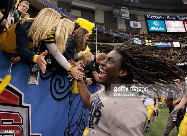 Denard Robinson of the Michigan Wolverines celebrates as he runs off of the field after Michigan won 23-20 in overtime against Virginia Tech Hokies...