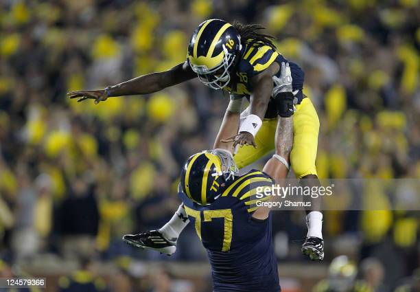 Denard Robinson of the Michigan Wolverines celebrates the game winning touchdown with Taylor Lewan to beat the Notre Dame Fighting Irish 3531 at...