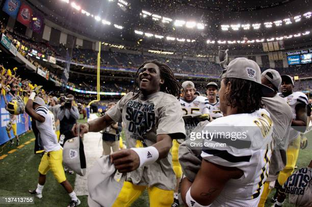 Denard Robinson of the Michigan Wolverines celebrates with his teammates after Michigan won 2320 in overtime against the Virginia Tech Hokies during...