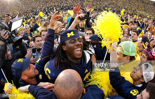 Denard Robinson of the Michigan Wolverines celebrates with students after beating Ohio State 4034 at Michigan Stadium on November 26 2011 in Ann...