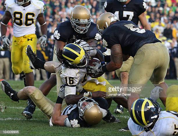 Denard Robinson of the Michigan Wolverines dives into the end zone for the game-winning touchdown as Harrison Smith of the Notre Dame Fighting Irish...