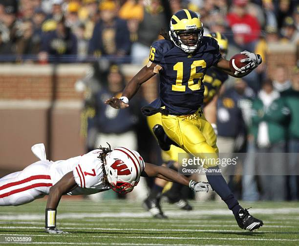 Denard Robinson of the Michigan Wolverines gets around the tackle of Aaron Henry of the Wisconsin Badgers at Michigan Stadium on November 20 2010 in...