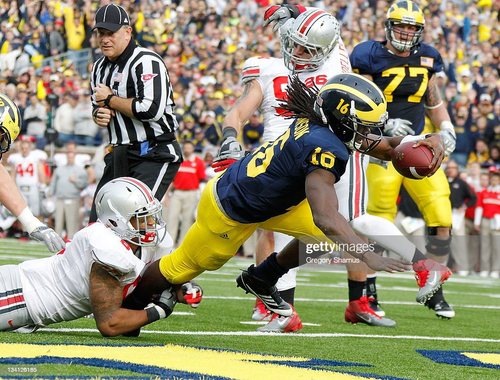Denard Robinson #16 of the Michigan Wolverines gets in for a second quarter touchdown past the tackle of Etienne Sabino #6 of the Ohio State Buckeyes at Michigan Stadium on November 26, 2011 in Ann Arbor, Michigan.