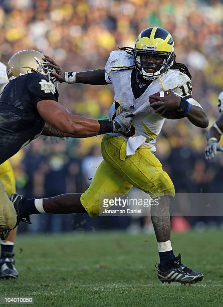 Denard Robinson of the Michigan Wolverines pushes off a tackle attempt by Manti Te'o of the Notre Dame Fighting Irish in the final minute at Notre...