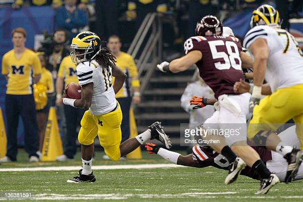 Denard Robinson of the Michigan Wolverines runs with the ball in the first quarter against the Virginia Tech Hokies during the Allstate Sugar Bowl at...