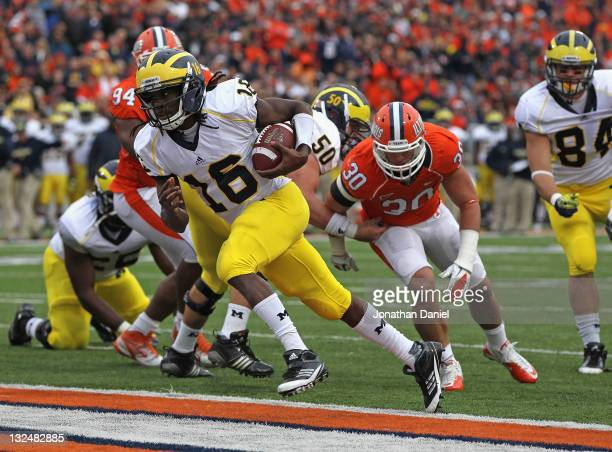 Denard Robinson of the Michigan Wolverines scores his second touchdown as he runs past Houston Bates of the Illinois Fighting Illini at Memorial...