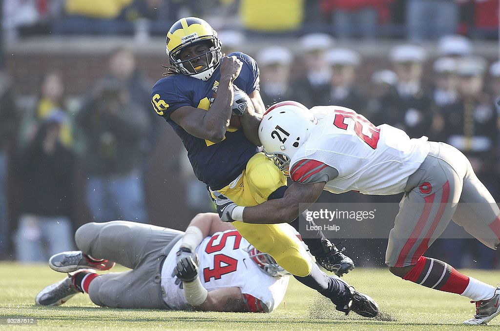 Denard Robinson #16 of the University of Michigan is tackled by Anderson Russell #21 and John Simon #54 of the Ohio State Buckeyes in the fourth quarter. The Ohio State defeated Michigan 21-10 at Michigan Stadium on November 21, 2009 in Ann Arbor, Michigan.