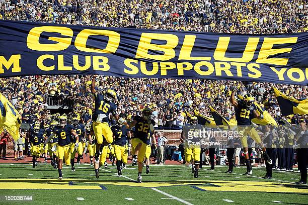Denard Robinson of the University of Michigan Wolverines leads his team to the field before a Big Ten College football game against the Univerity of...
