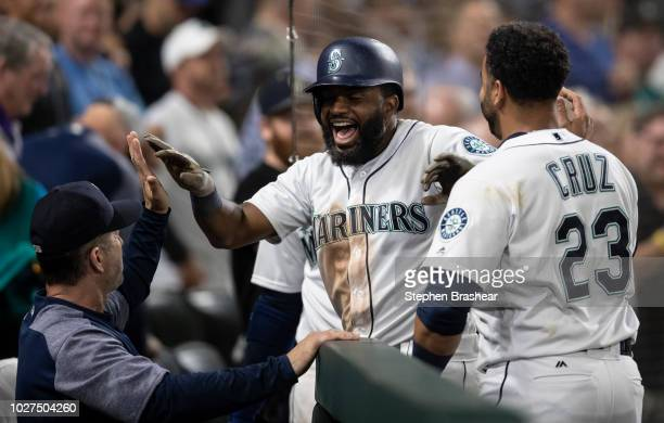 Denard Span of the Seattle Mariners is congratulated by hitting coach Edgar Martinez and Nelson Cruz of the Seattle Mariners after hitting solo home...