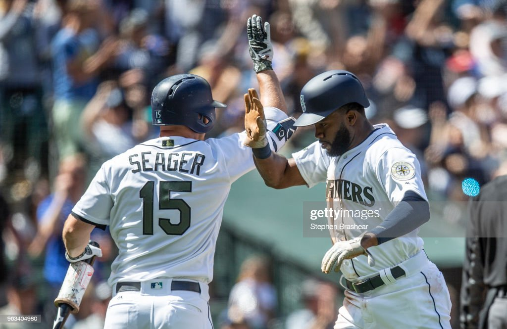 Denard Span #4 of the Seattle Mariners is congratulated by Kyle Seager #15 of the Seattle Mariners after scoring a run on a hit by Nelson Cruz #23 of the Seattle Mariners off of starting pitcher Doug Fister #38 of the Texas Rangers during the sixth inning of a game at Safeco Field on May 28, 2018 in Seattle, Washington. The Mariners won the game 2-1. MLB players across the league are wearing special uniforms to commemorate Memorial Day.