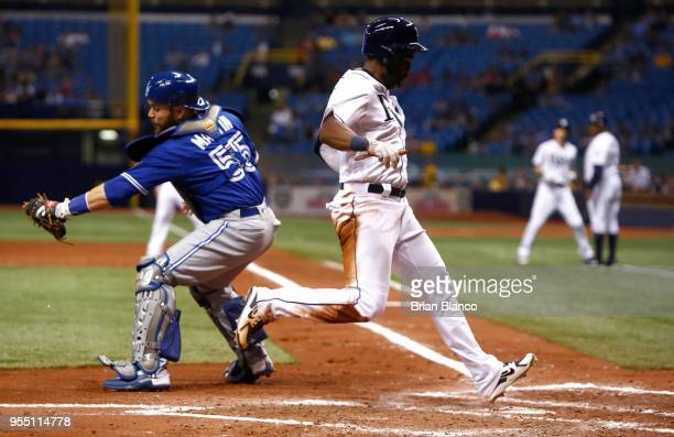 Denard Span of the Tampa Bay Rays beats catcher Russell Martin of the Toronto Blue Jays to home plate as he scores off of a sacrifice fly by Matt...