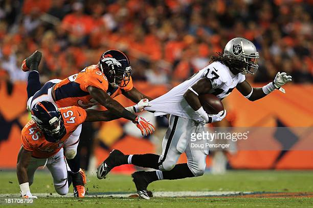 Denarius Moore of the Oakland Raiders breaks the tackle of Duke Ihenacho and Dominique Rodgers-Cromartie of the Denver Broncos to run in a 73 yard...