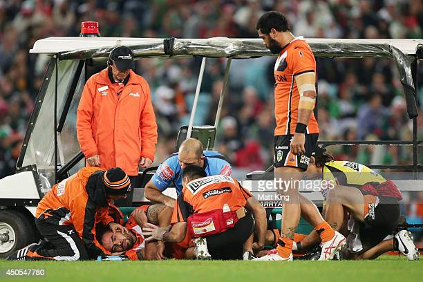 Dene Halatau of the Tigers is assisted on the field after sustaining an injury during the round 14 NRL match between the South Sydney Rabbitohs and...