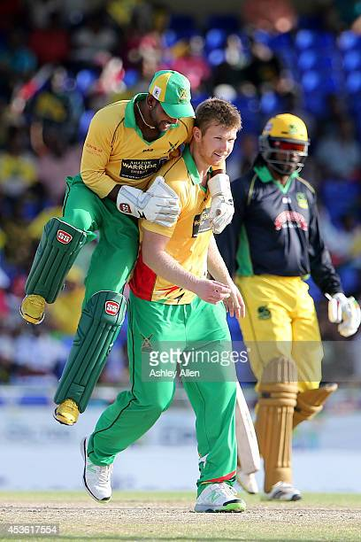 Denesh Ramdin celebrates with team mate Jimmy Neesham as he gets the wicket of Chris Gayle during a Semifinal match between Jamaica Tallawahs and...