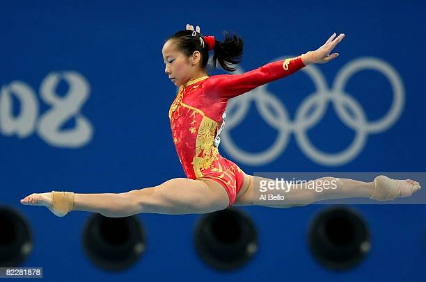 Deng Linlin of China performs on the balance beam during the women's team final of the artistic gymnastics event at the National Indoor Stadium...