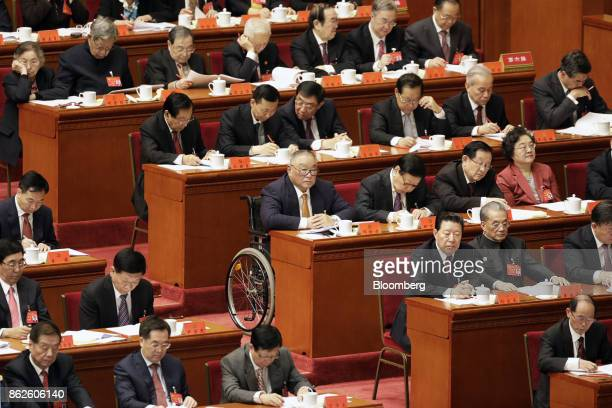 Deng Pufang, eldest son of the late Deng Xiaoping, China's former paramount leader, center, sits along with other delegates as they attend the...