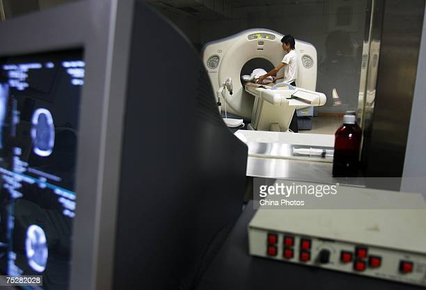 Deng Weijun father of quadruplets supports one of his babies during a CT scan at Tongji Hospital July 9 2007 in Wuhan of Hubei Province China...