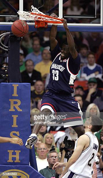 Denham Brown of the Connecticut Huskies slams the ball over Chris Quinn of the Notre Dame Fighting Irish on January 30 2005 at the Joyce Center at...