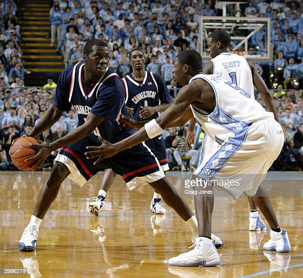Denham Brown of the University of Connecitcut Huskies holds the ball as he is covered by Jackie Manuel of the Universtiy of North Carolina Tar Heels...