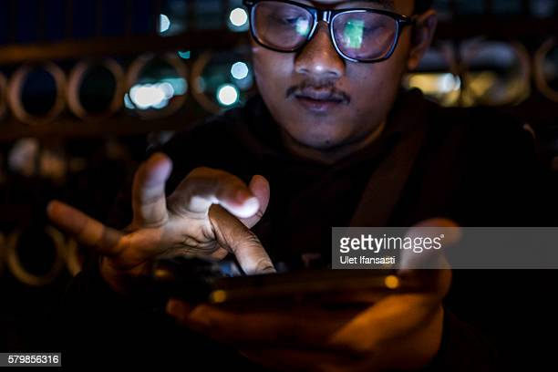 Deni plays Pokemon Go game on his smartphone on July 24 2016 in Yogyakarta Indonesia Pokemon Go which uses Google Maps and a smartphone has been a...